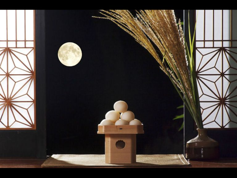 White Dango are stacked in a pyramid shape, next to a vase with decorative grass.