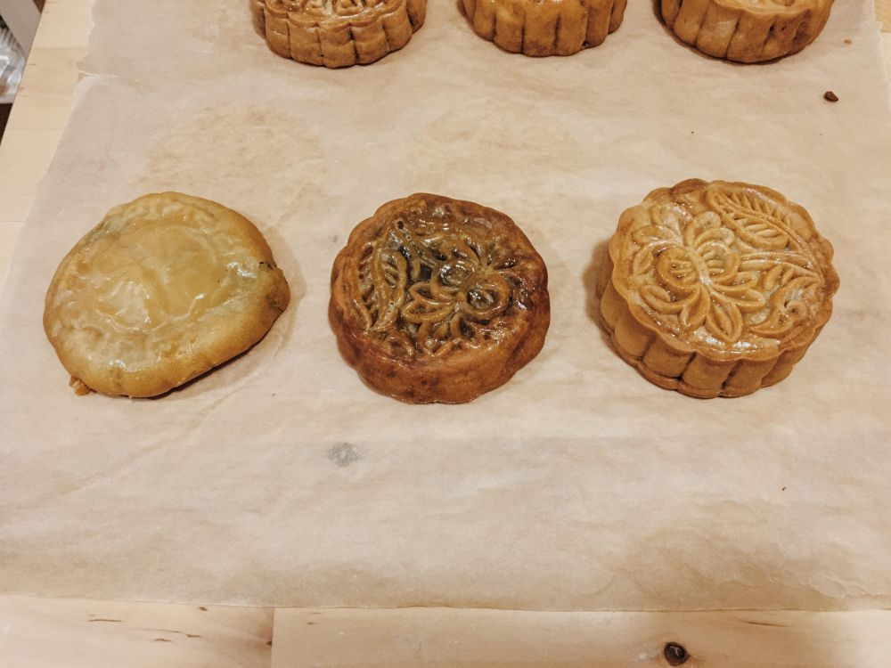 "Three mooncakes in a row. The one on the left is misshapen and does not have a clear pattern. The middle mooncake has a slightly more visible pattern. The right most one has a clearly visible pattern, and looks most ""mooncake-like"""