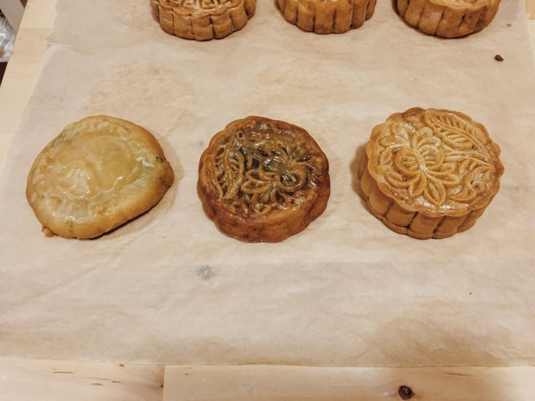 """Three mooncakes in a row. The one on the left is misshapen and does not have a clear pattern. The middle mooncake has a slightly more visible pattern. The right most one has a clearly visible pattern, and looks most """"mooncake-like"""""""