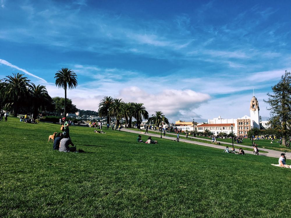 A picture of a green grassy hill, with Mission High School in the background.