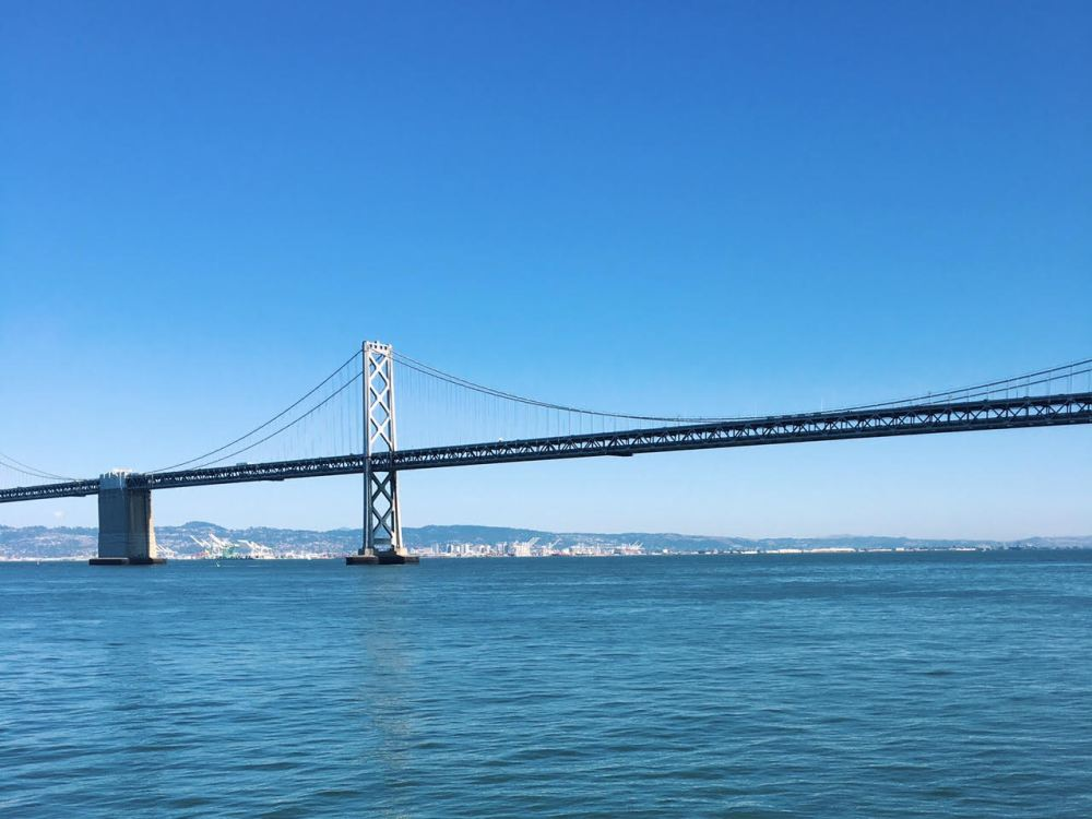 A photo of the Bay Bridge, with West Oakland visible in the horizon.