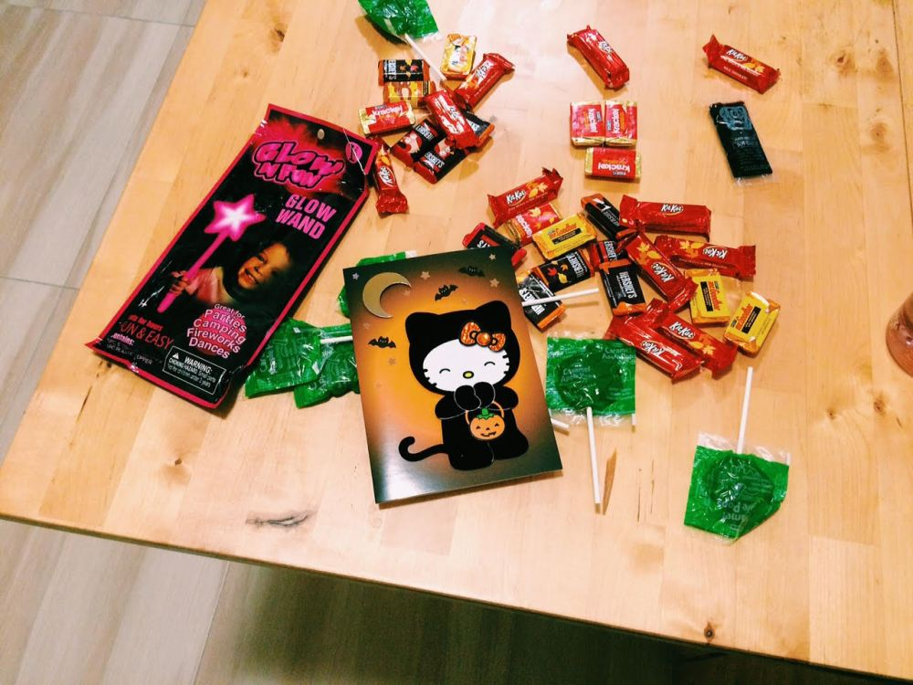 Halloween Candy, a Hello Kitty Halloween Card and a Glow Stick on a wooden table.