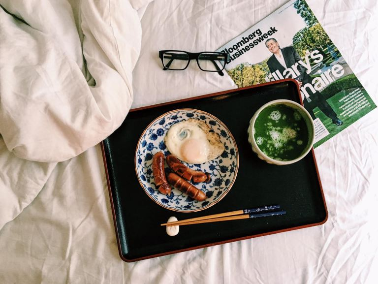 A resin tray on a bed. There is a plate with an egg and a sausage on the tray, and a cup of green tea.
